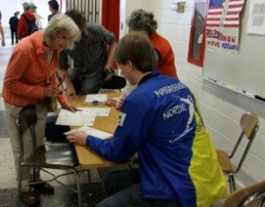 Phyllis Riley helps students register to vote.
